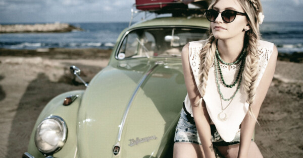 5 Simple Summer Skincare Tips- blonde young girl sitting on the hood of VW Bug at beach