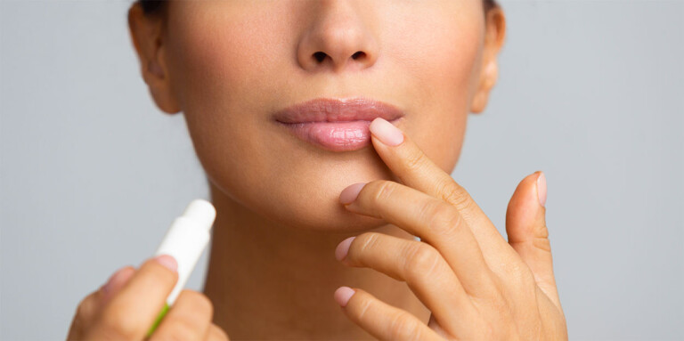 clean beauty products - woman applying lip balm