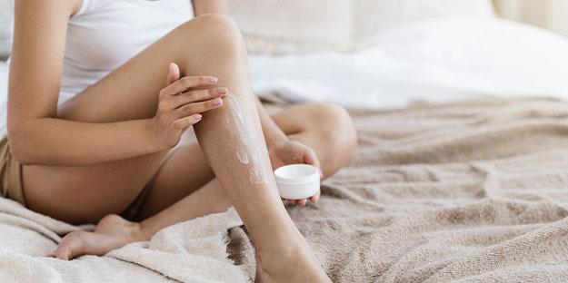 clean beauty products-woman applying lotion to legs
