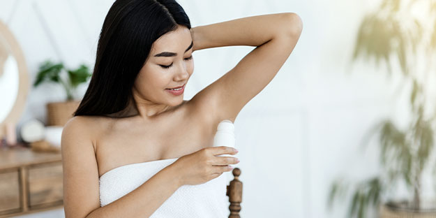 clean beauty products-woman using deodorant